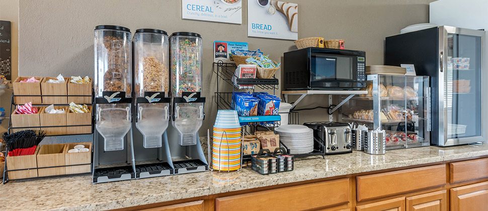 Cereal dispensors lined up on a counter in a breakfast area at the lodge.