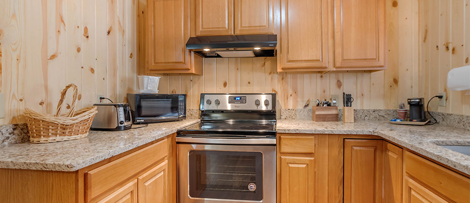 A kitchenette with granite countertop featuring a range, and kitchen appliances with utensils and flatware next to stove.