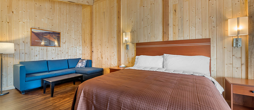 A bare wood room accented by brown bed and bed spread, and blue sofa in the corner. Lamps and artwork lightly grace the walls surrounding the bed.