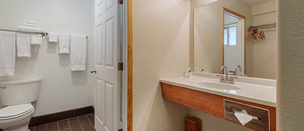 A wall mounted sink with full size mirror. Door opens into the commode.