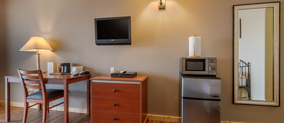 A television on the wall above a dresser is flanked by a small sitting area and a microwave atop a mini-fridge.