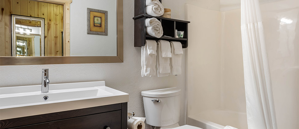 A well appointed bathroom with dark stained sink cabinet, wide frame mirror, and rustic towel holder above the commode and next to the shower.