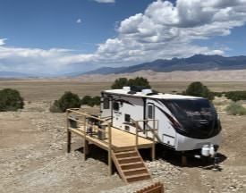 Camper and wooden deck with sand dunes and mountains in background