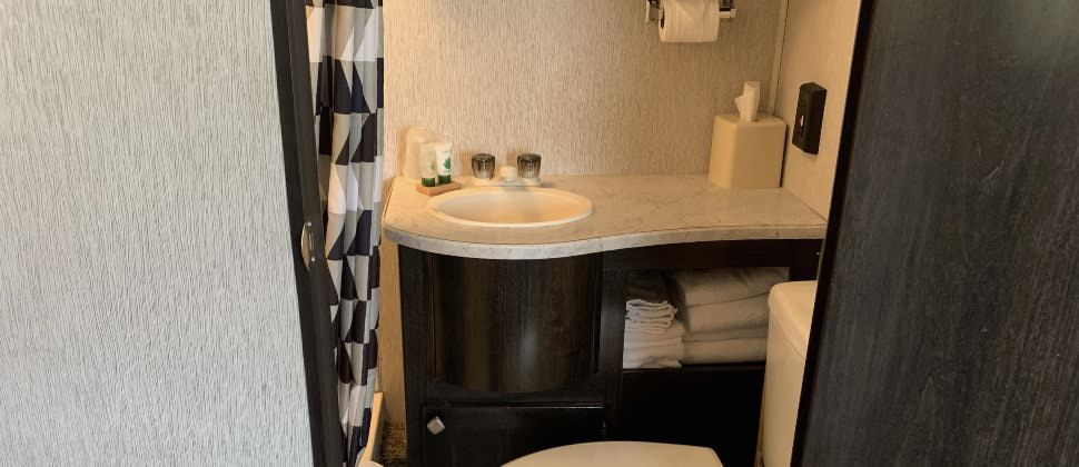 Bathroom in camper with dark wooden cabinets, cream sink and toilet, and black, white, and tan shower curtain